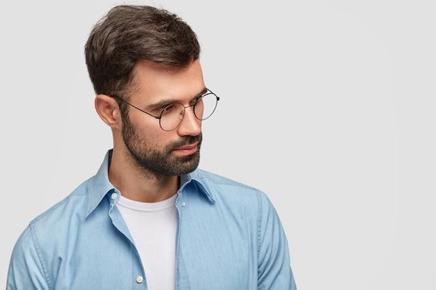 Photo de jeune homme mal rasé avec chaume et cheveux foncés, porte des lunettes et une chemise, concentré sur le côté, pose contre le mur blanc