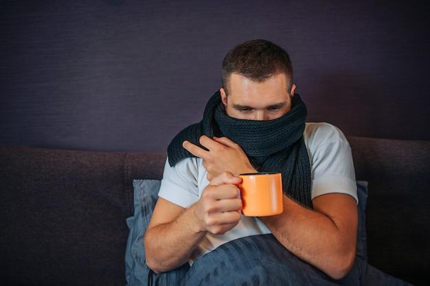 Photo de jeune homme malade assis sur le lit et tenant une tasse de thé orange. il le regarde. guy se couvre la bouche avec un foulard. il a eu froid.