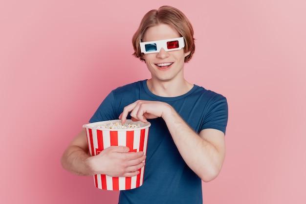 Photo de jeune homme manger du pop-corn heureux sourire positif porter des lunettes 3d regarder cinéma isolé sur fond de couleur rose