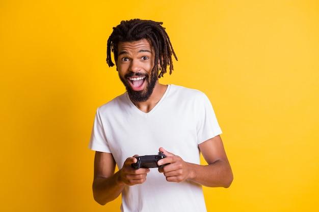 Photo d'un jeune homme noir tenir la manette du doigt du contrôleur bouche ouverte porter un t-shirt blanc isolé sur fond de couleur jaune