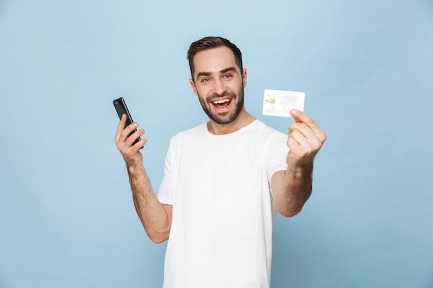Photo d'un jeune homme de race blanche en t-shirt blanc décontracté se réjouissant tout en tenant une carte de crédit et un smartphone isolés sur un mur bleu