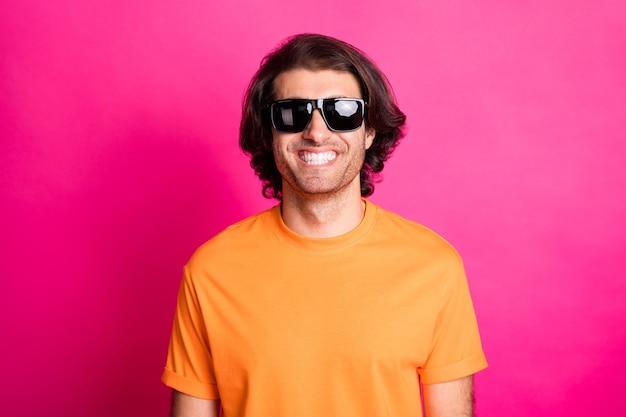 Photo de jeune homme regarder caméra sourire blanc porter des lunettes de soleil orange t-shirt isolé fond de couleur rose