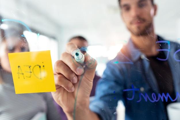 Photo d'un jeune homme réussi écrivant sur une planche de verre de bureau lors de la réunion avec des collègues dans l'espace de coworking.
