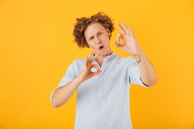Photo de jeune homme satisfait souriant et montrant signe ok avec les doigts à la caméra, isolé sur fond jaune