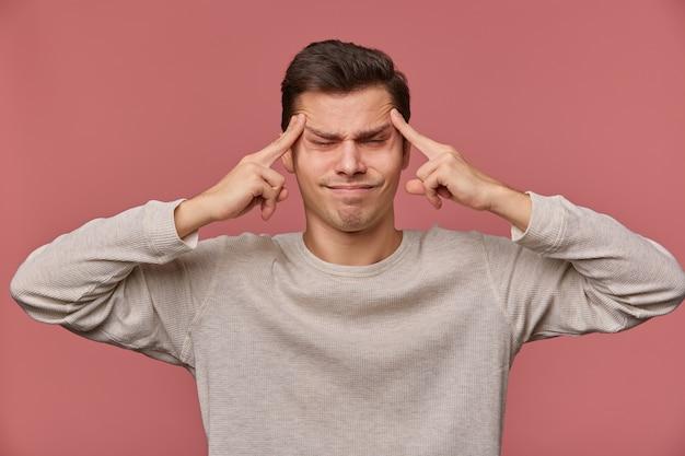 Photo de jeune homme séduisant en blanc à manches longues, se dresse sur fond rose et montre le geste de headshot avec les yeux fermés, se sent anhappy et migraineã'âž