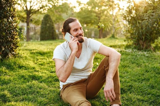 Photo de jeune homme sociable en tenue décontractée assis sur l'herbe dans le parc verdoyant, et parlant sur smartphone avec plaisir
