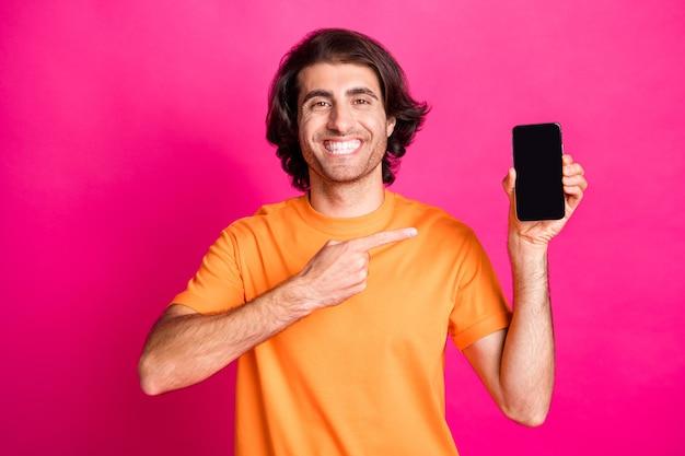 Photo de jeune homme tenir le téléphone indiquer l'espace vide de l'écran du doigt porter un t-shirt orange isolé sur fond de couleur rose
