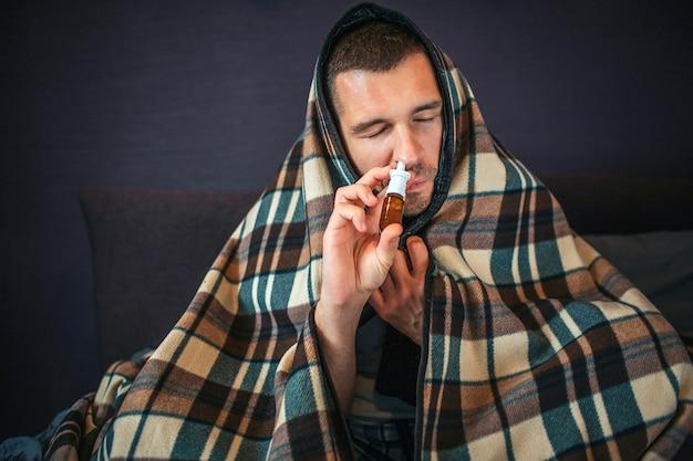 Photo d'un jeune homme tout couvert de couverture. il utilise un spray nasal. guy rétrécit et garde les yeux fermés. young mean fait un peu de traitement pour être en bonne santé.