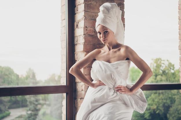 Photo de jeune jolie dame séduisante procédures de maison de spa quarantaine rester à la maison beauté nue épaules posant porter seulement une couverture tête turban salon grande fenêtre à l'intérieur