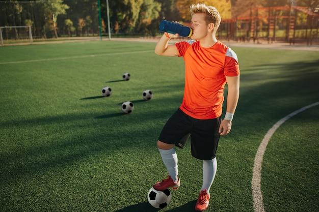Photo de jeune joueur de football se tenir debout sur la pelouse et boire de l'eau. il tient les pieds sur le ballon. quatre autres balles sont derrière. temps d'été ensoleillé en dehors.