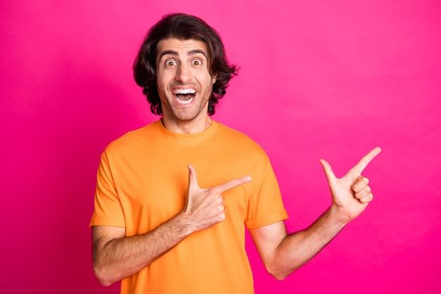 Photo de jeune mec à poils directs doigts espace vide bouche ouverte porter un t-shirt orange isolé sur fond de couleur rose