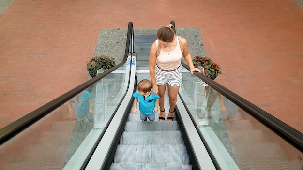 Photo d'une jeune mère tenant son petit fils à la main en montant sur l'escalator du centre commercial