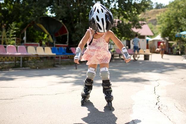 Photo d'un jeune patineur à roulettes en dehors du patinage seul. tout-petit professionnel dans l'équipement de patinage s'amuse à monter. soleil et été.