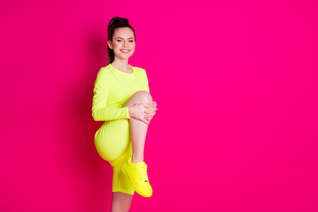 Photo de jeune sportive positive jambe étirée espace vide isolé sur fond de couleur rose vif