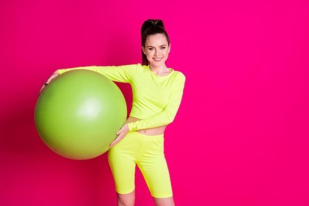 Photo de jeune sportive positive tenir fitball porter un short jaune isolé sur fond de couleur rose vif