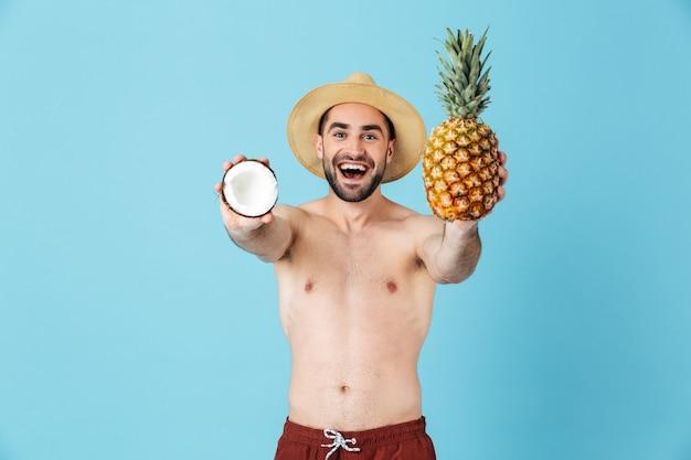 Photo d'un jeune touriste torse nu portant un chapeau de paille souriant tout en tenant des fruits exotiques isolés sur bleu