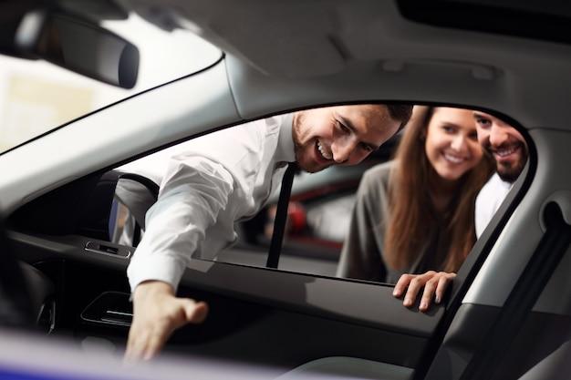 Photo d'un jeune vendeur confiant expliquant toutes les caractéristiques de la voiture aux jeunes propriétaires attrayants