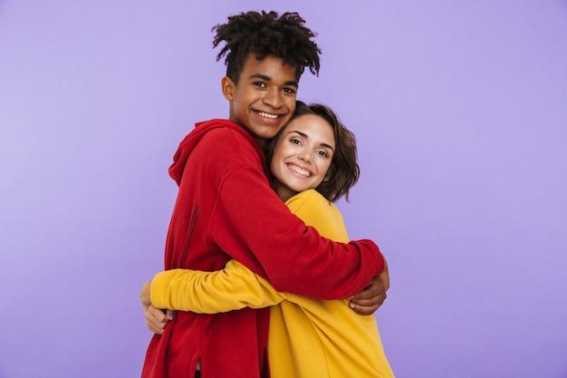 Photo de jeunes étudiants amis couple debout isolés, étreignant.