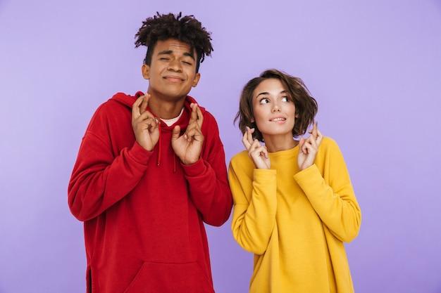 Photo de jeunes étudiants amis couple debout isolés, montrant un geste d'espoir.
