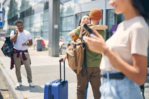 Photo de jeunes femmes et hommes avec une valise étreignant à l'extérieur où des amis heureux de se voir