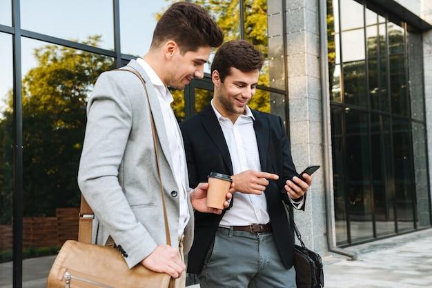 Photo de jeunes hommes d'affaires en costumes à l'aide de smartphones, tout en se tenant à l'extérieur près du bâtiment avec du café à emporter