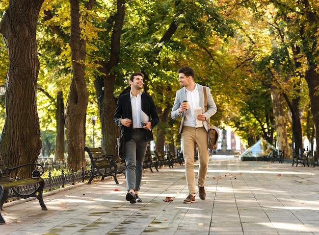 Photo de jeunes hommes d'affaires en costumes marchant en plein air à travers le parc verdoyant avec café à emporter et ordinateur portable, pendant la journée ensoleillée