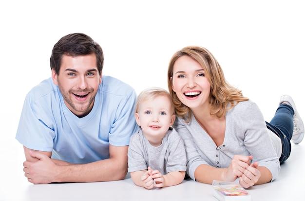 Photo des jeunes parents souriants avec petit enfant allongé sur le sol - isolé