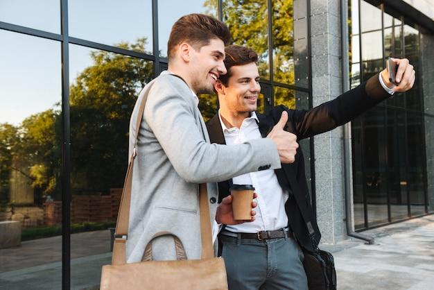 Photo de jeunes partenaires commerciaux en costume à l'aide de smartphones pour selfie, debout à l'extérieur près du bâtiment avec du café à emporter