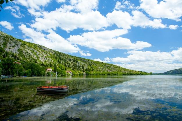 Photo d'un joli bateau dans la mer sur le magnifique fond d'île sous le soleil de la grèce
