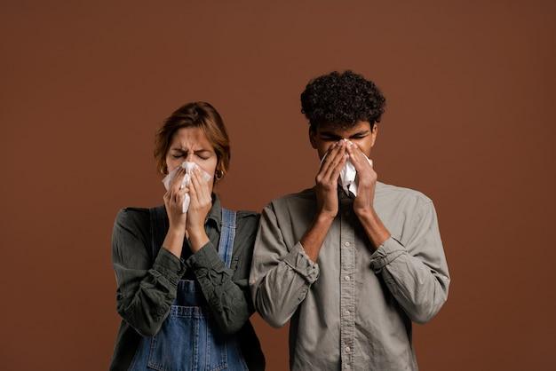 Photo d'un joli couple d'agriculteurs, qui se sont mouchetés et sont tombés malades. la femme porte une salopette en denim, l'homme porte un t-shirt isolé sur fond de couleur marron.