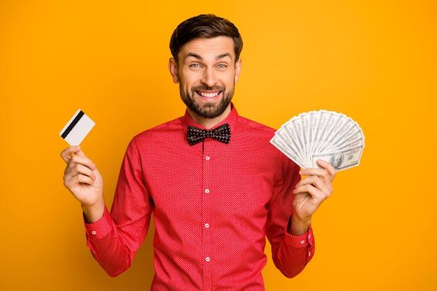 Photo de joli drôle de gars tenir fan de dollars américains nouvelle carte de crédit en plastique riche acheteur porter chemise rouge à la mode noeud papillon vêtements