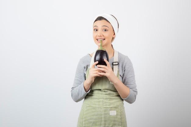 Photo d'un joli modèle de jeune femme en tablier tenant une aubergine