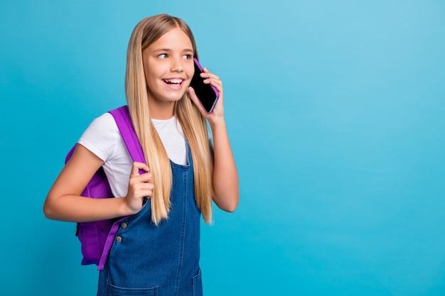 Photo d'une jolie adolescente cool à la recherche d'un espace vide parler de téléphone porter une robe en jean isolée sur fond de couleur bleu pastel