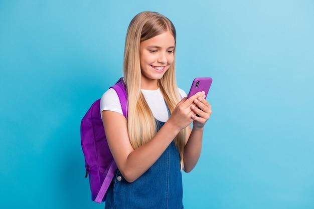 Photo d'une jolie adolescente optimiste à la recherche d'une robe en jean sac d'usure de téléphone isolée sur fond de couleur bleu pastel