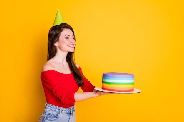 Photo de jolie adorable jeune fille joyeuse souriante brillante acceptant les cadeaux d'anniversaire tenir le gâteau porter une chemise de cône épaules ouvertes jupe en jean isolé fond de couleur jaune vif