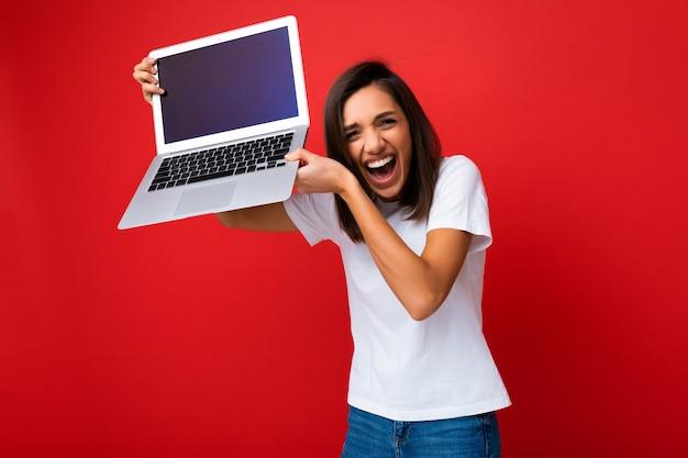 Photo d'une jolie belle jeune femme ravie et heureuse avec une courte coupe de cheveux brun foncé tenant un ordinateur portable jusqu'à la tête en regardant la caméra portant un t-shirt blanc et un jean isolé sur fond de mur rouge