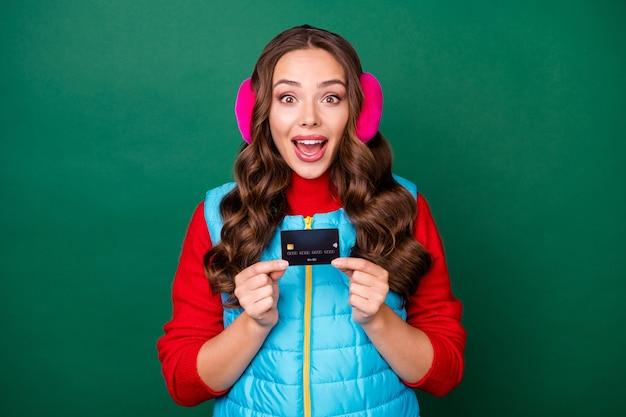 Photo de jolie charmante jeune femme excitée bouche ouverte tenir une carte de crédit montrant une option limitée shopping parfait porter des cache-oreilles roses gilet bleu pull rouge isolé fond de couleur verte