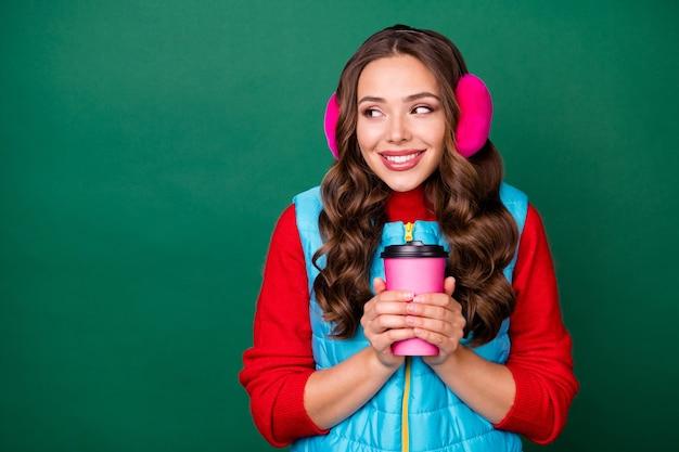 Photo de jolie charmante jeune femme tenir une tasse de café à emporter regarder un espace vide rayonnant souriant parc d'hiver marcher porter des cache-oreilles roses gilet bleu pull rouge isolé fond de couleur verte