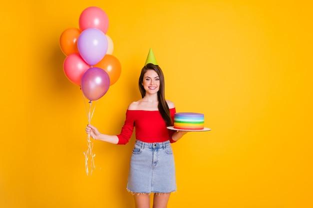 Photo de jolie charmante jeune fille joyeuse souriante brillante tenir de nombreux ballons concept d'anniversaire de gâteau porter une chemise de cône épaules ouvertes jupe en jean isolé fond de couleur jaune vif