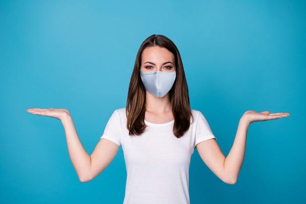 Photo de jolie dame de bonne humeur tenir les paumes ouvertes les bras montrant sélectionner choisir nouveauté covid infection arrêter les produits porter un masque médical t-shirt blanc décontracté fond de couleur bleu isolé