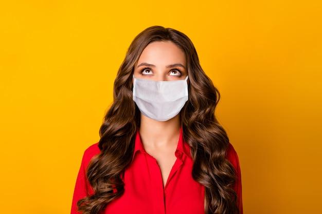 Photo d'une jolie dame bouclée rechercher un espace vide intéressé par les nouvelles covid porter un masque médical vêtement de cérémonie chemise de bureau rouge isolé fond de couleur jaune vif