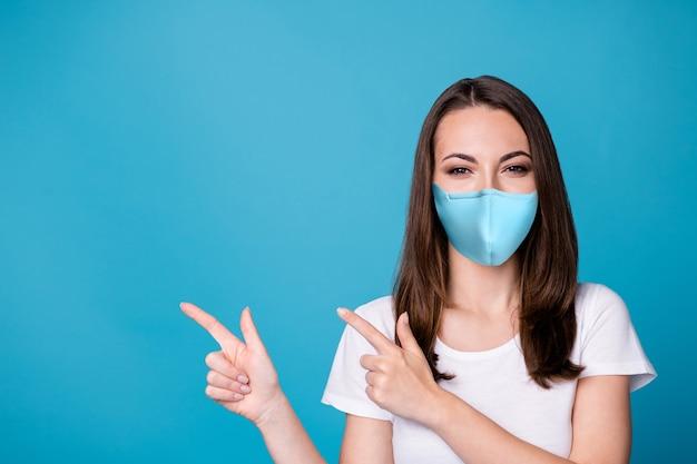 Photo d'une jolie dame charmante assez drôle de bonne humeur dirigeant les doigts côté espace vide montrant la nouveauté covid porter un masque médical blanc décontracté t-shirt isolé fond de couleur bleu