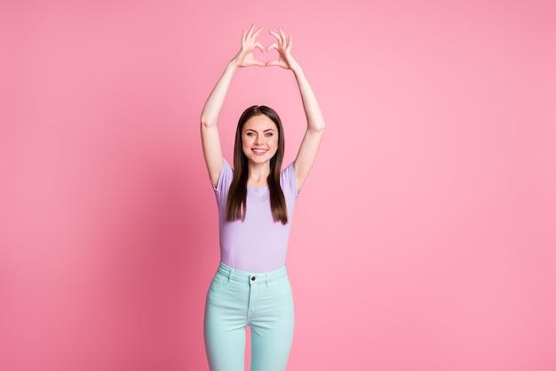 Photo d'une jolie dame charmante faire des bras en forme de coeur figure humeur romantique invitant un petit ami date porter un t-shirt violet décontracté pantalon sarcelle isolé fond de couleur pastel rose