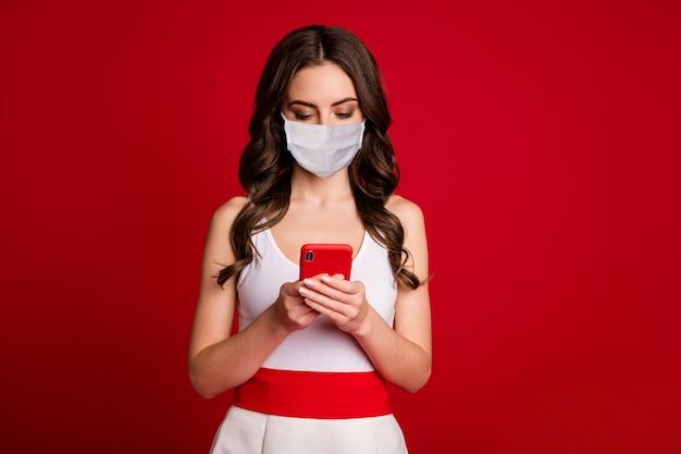 Photo d'une jolie dame charmante millénaire utiliser des mains de téléphone discutant des amis lire un message en tapant réponse covid quarantaine porter un masque médical robe blanche isolée fond de couleur rouge vif