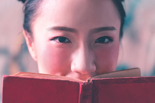 Photo d'une jolie dame chinoise couvrant le visage avec un livre rouge.