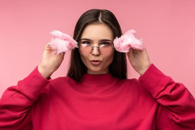 Photo de jolie dame dans des verres joue avec des bonbons de barbe à papa a du plaisir à porter un pull rose décontracté isolé sur fond de couleur rose.