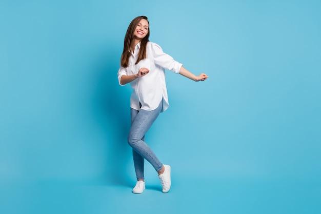 Photo de jolie dame danse étudiants fête fou de joie porter chemise blanche jeans baskets isolé fond de couleur bleu