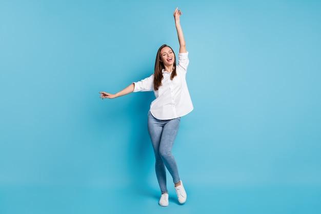 Photo de jolie dame drôle danse porter chemise blanche jeans baskets fond de couleur bleu isolé