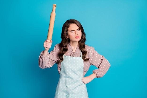 Photo de jolie dame folle en colère tenir la main ustensile de cuisine rouleau à pâtisserie cuisson gâteau tarte vouloir battre petit ami pour déranger porter tablier robe à pois isolé fond de couleur bleu