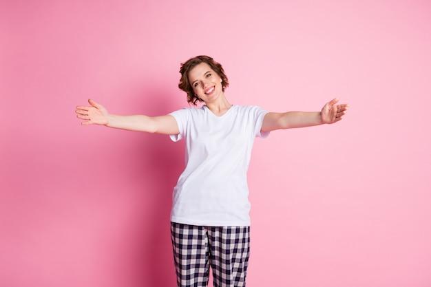Photo de jolie dame inviter étirer les mains sur le mur rose